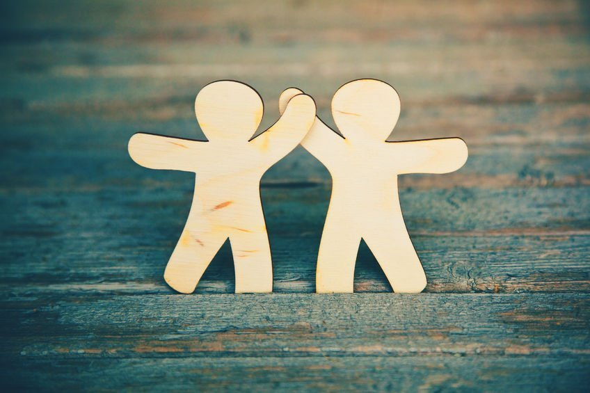 46651291 - wooden little men holding hands on wooden boards background. symbol of friendship, love and teamwork